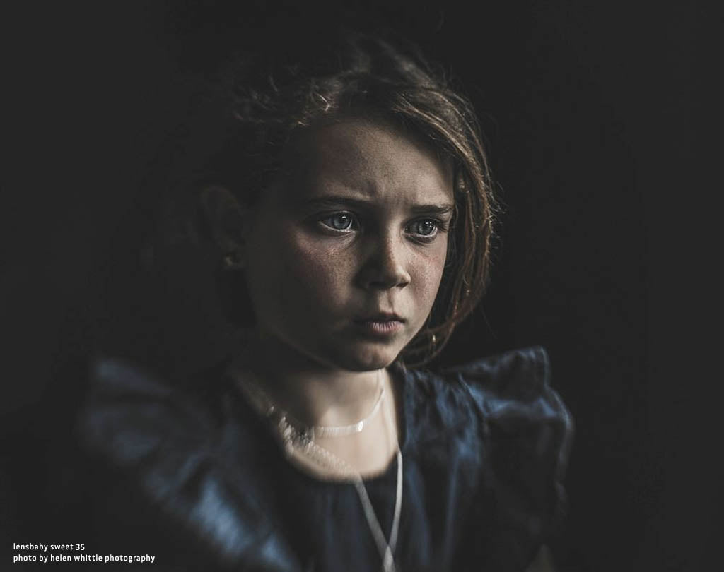 young girl with a serious expression dark background dark dress confused thinking Lensbaby Top 12 Photos