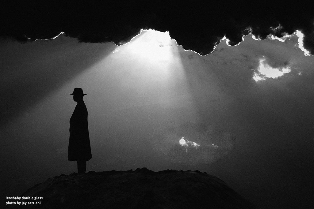 man in hat and trench coat silhouette sun rays from clouds black and white lensbaby manifesto struggle