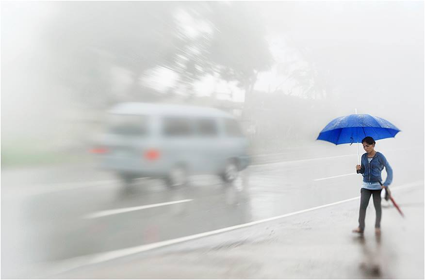 man with blue umbrella blue sweatshirt rainy street scene featured photos of the week we are the enemy of perfection