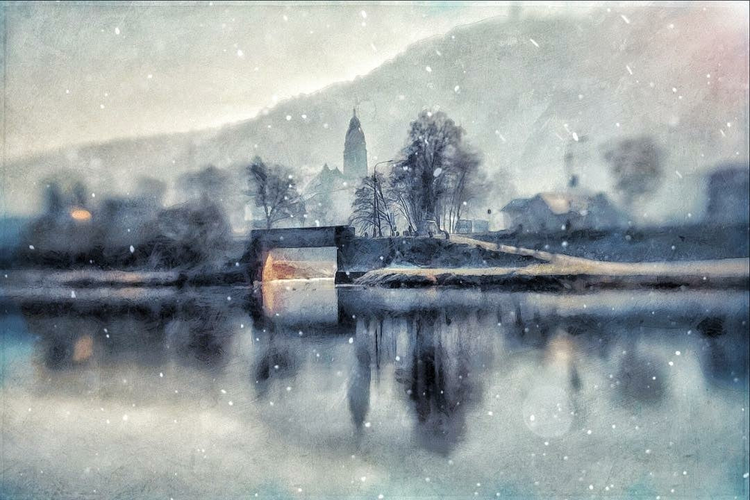 small town on the edge of a lake with trees and snow falling featured photos discovery is our joy