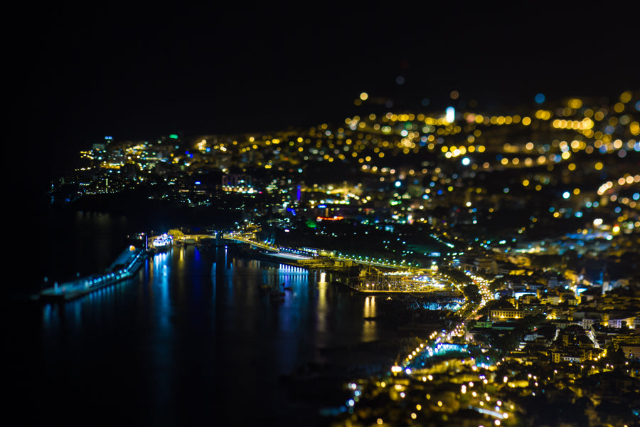 Coastal port of Funchal at night, bright city lights on a black backdrop photographed in Lensbaby tilt shift lens style by Nuno Caldeira.