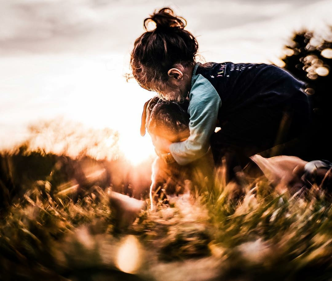 young girl with pug dog sunset backpack hug grass light flare twist Lensbaby featured photos