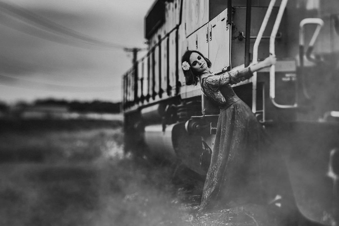 woman in long vintage dress hanging from a train flower in hair black and white lensbaby featured photos