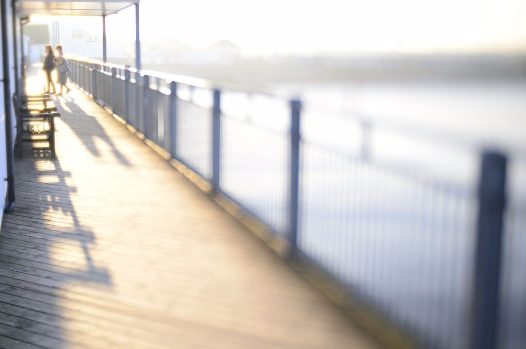 Southwold Pier light and shadows on a dock railing people selective focus Lensbaby featured photos