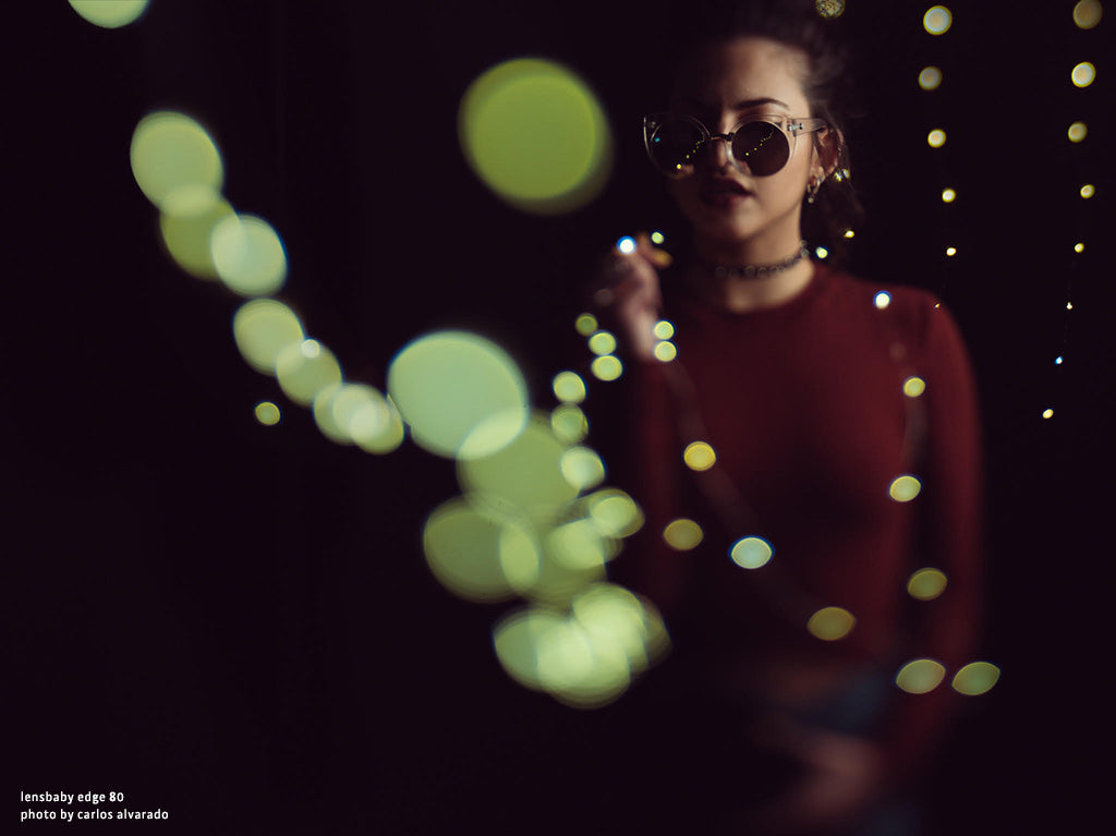 Woman with big sunglasses glowing green lights lensbaby manifesto discovery is our joy