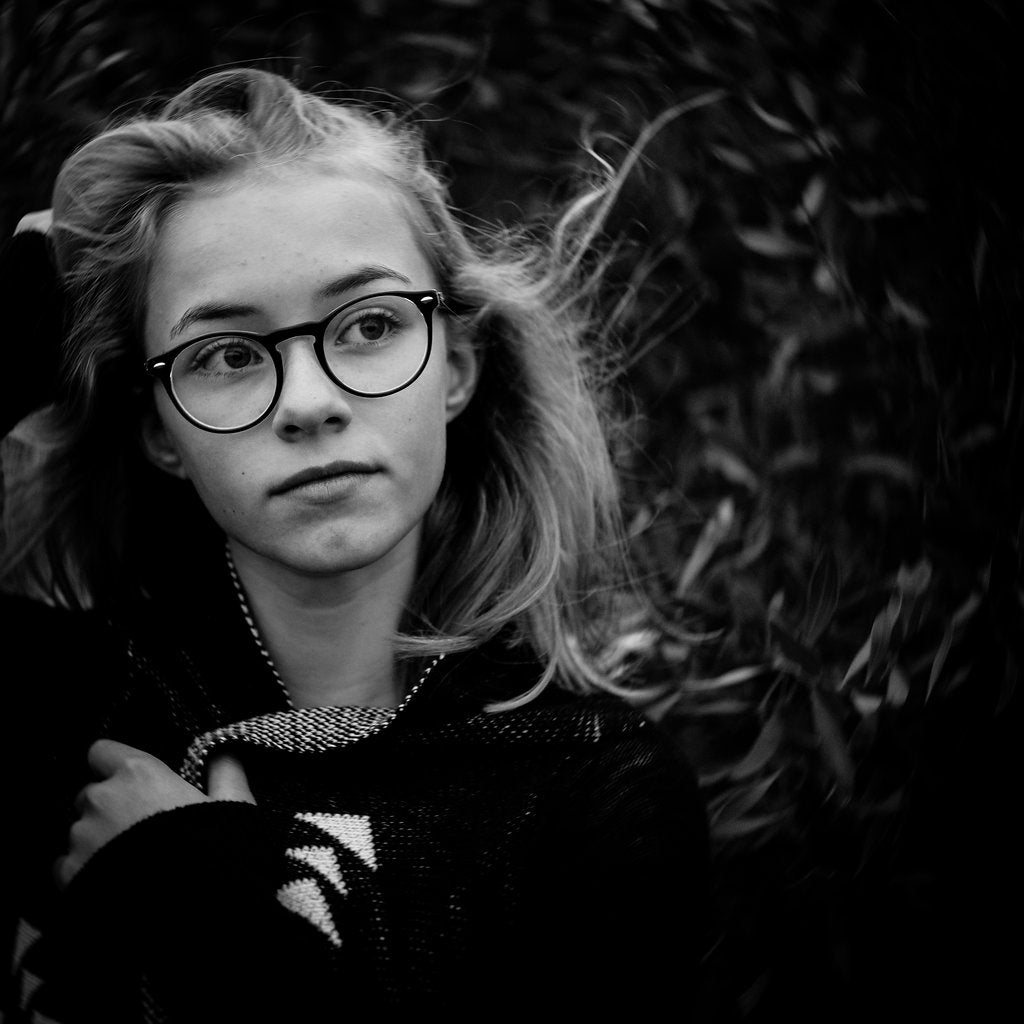 Fine art photograhy by Ute Reckhorn of a teenager in glasses with her hair blowing in the in wind staring off into the forest shot using the Lensbaby Twist 60.