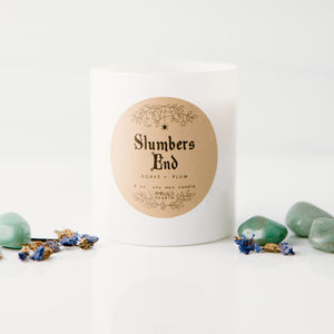 Front image of the Slumbers End candle by Emerald Hearth.  This white candle is photographed against a white background and is surrounded by flower buds and green stones.  Slumbers End is adorned with Green Aventurine and a violet Forget Me Not flower to support budding confidence in your new intentions for the coming months. 8oz 50+ hours of burn time Limited Edition Annual Release