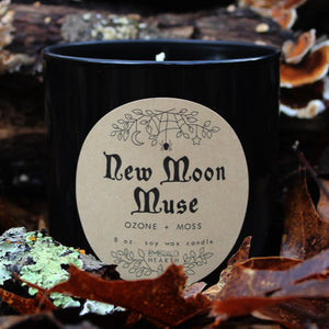 The Emerald Hearth New Moon Muse candle in black surrounded by leaves.  This candle has notes of ozone and moss.