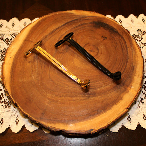 Emerald Hearth candle wick trimmers photographed on a slab of wood.  The two trimmers are in gold and black.