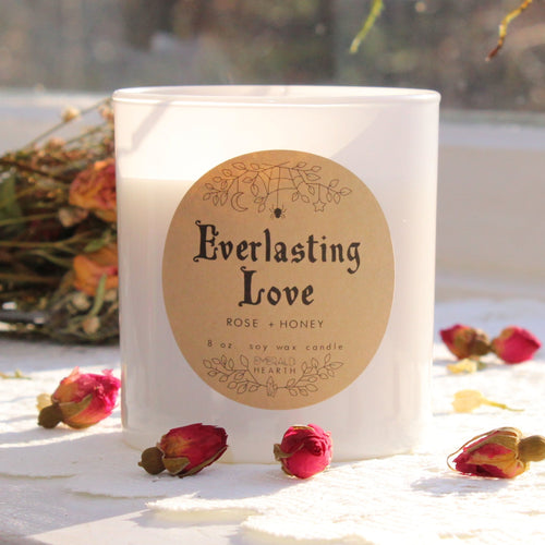 The white Everlasting Love candle with rosebuds around it photographed in the sunlight.  This candle is by Emerald Hearth Creations.