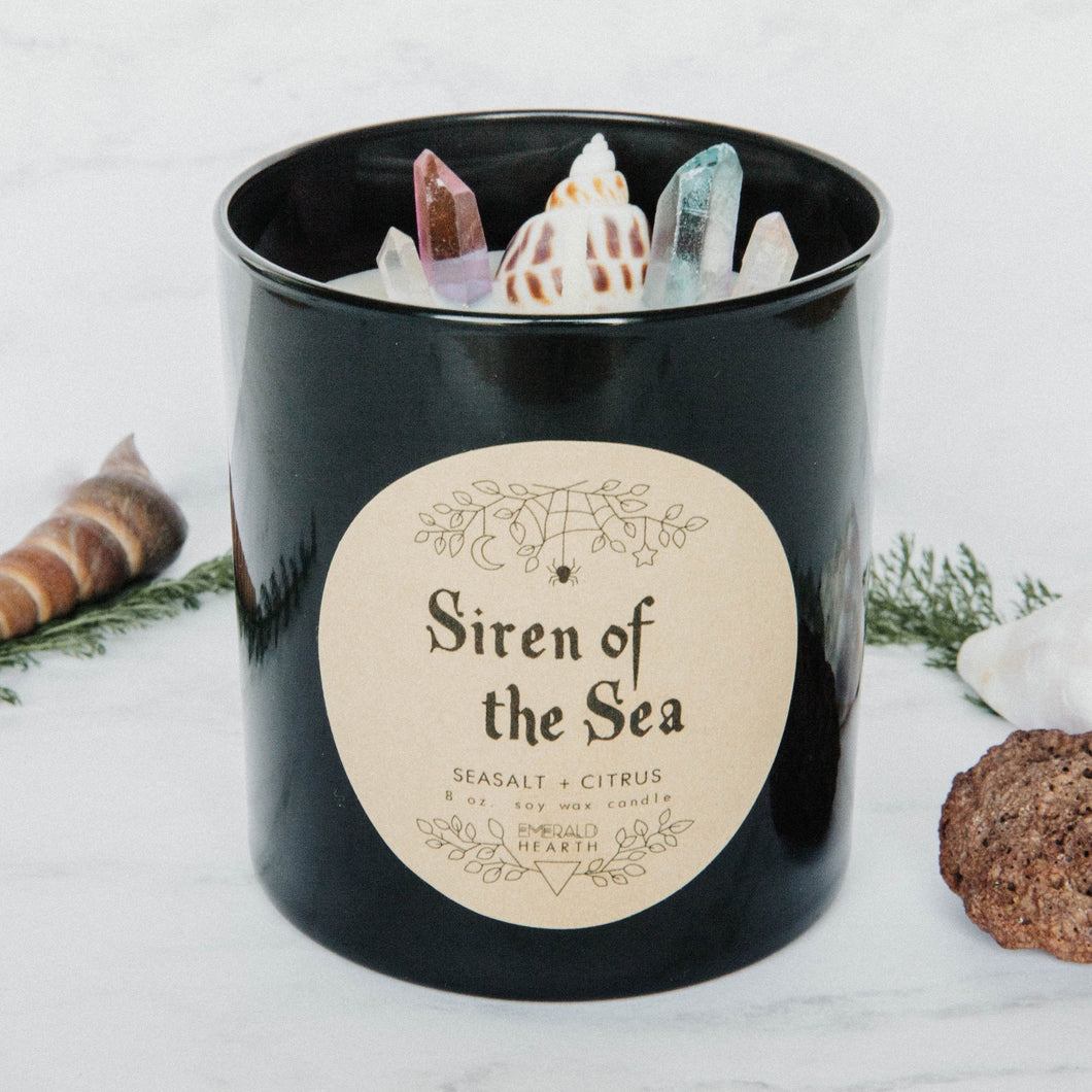 Image of the Siren of the Sea candle by Emerald Hearth.  This candle has bits of quartz and a seashell on the top.
