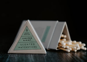 Image of Juniper & Mint scented match sticks.  The lid of the triangle packaging is in the foreground and in focus.  The background is of the matches which is out of focus.