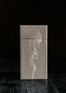 Side view of the Juniper and Mint scented matchsticks.  There is also a puff of smoke in front.