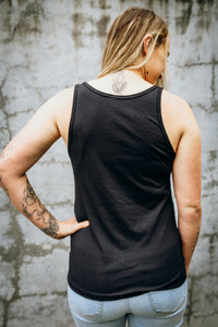 A woman wearing an Emerald Hearth tank top that says Magic Surrounds Me. The woman is standing facing away from the camera and the back of the tank top is blank.
