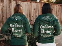 Load image into Gallery viewer, Two people wearing green Emerald Hearth hoodies facing away from the camera.  The hoodies have a spider web detail, the Emerald Hearth Logo, and the words: Goddess Rising.