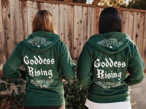 Two people wearing green Emerald Hearth hoodies facing away from the camera.  The hoodies have a spider web detail, the Emerald Hearth Logo, and the words: Goddess Rising.