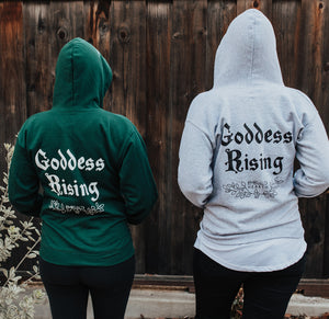Two people wearing Emerald Hearth hoodies (one in green and one in gray) facing away from the camera.  The hoodies have a spider web detail, the Emerald Hearth Logo, and the words: Goddess Rising.
