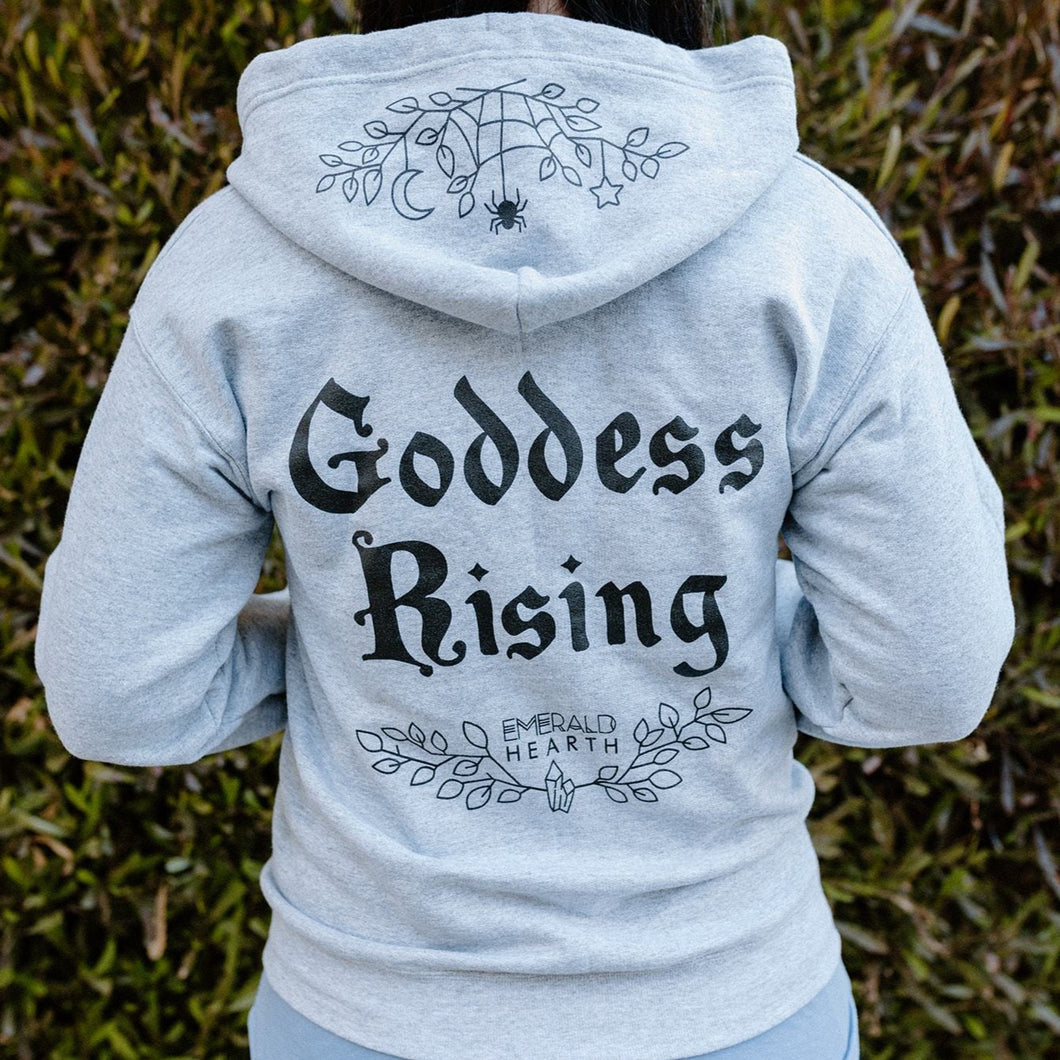 The back of the gray Emerald Hearth Zip Up Hoodie which says the words Goddess Rising in the center.  It has the logo underneath and features a spider web detail on the hood.