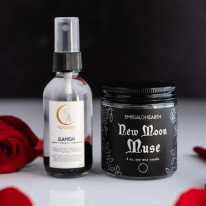 Photo of the New Moon Muse candle and the Banish aromatherapy spray photographed with roses.  Candle is by Emerald Hearth Creations.