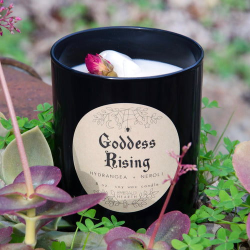 Image of the Emerald Hearth Goddess Rising Candle in black.  The candle is in a garden.  The rose bud on top is visible.