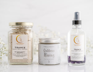 The Self Love Bath Bundle sold by Emerald Hearth. From left to right, the products displayed are the Trance Coconut Milk Bath, The Goddess Rising Candle, and the Trance Aromatherapy Spray.