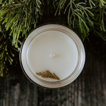 Cargar imagen en el visor de la galería, The top of the mini Flourishing Forest candle. The top of the candle has a spruce tip on it. The candle is placed next to some spruce.