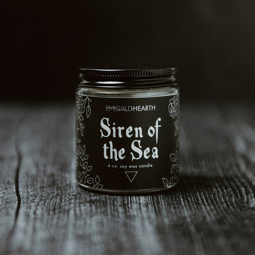 Front of the Siren of the Sea candle.  The candle's packaging is black.  This candle pulls inspiration from the ocean.