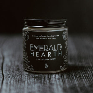 The mini Emerald Hearth original candle photographed on wood with a black background.
