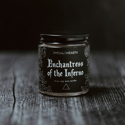 The mini Enchantress of the Inferno candle photographed on wood with a black background.