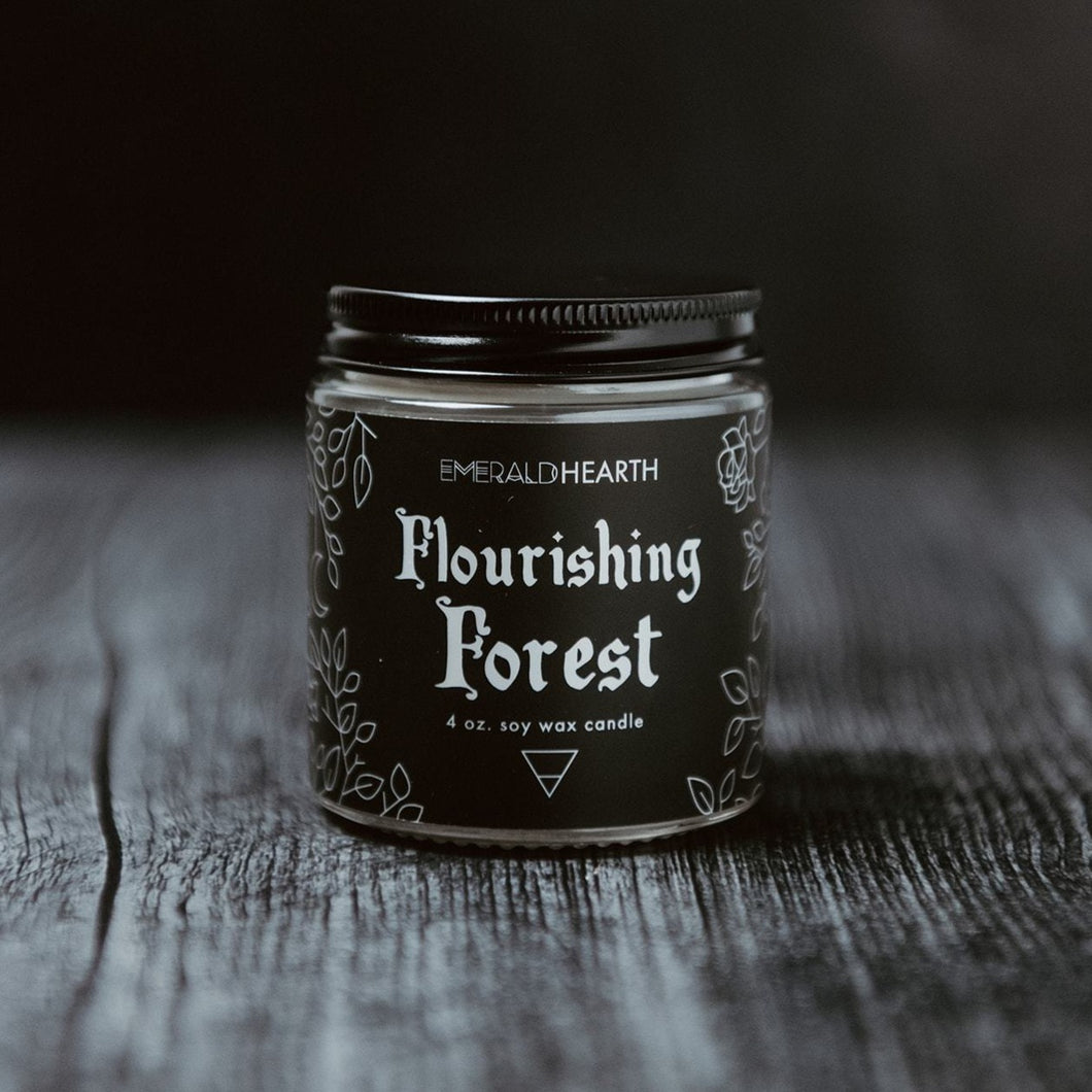 The mini 4oz version of the Emerald Hearth candle, Flourishing Forest.  The candle is photographed on wood with a black background.