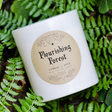 Cargar imagen en el visor de la galería, The white Flourishing Forest candle photographed against greenery.