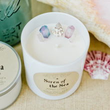 Load image into Gallery viewer, Image of the Siren of the Sea candle by Emerald Hearth.This candle is adorned with titanium-coated, pastel quartz nestled around a seashell to represent the water element.