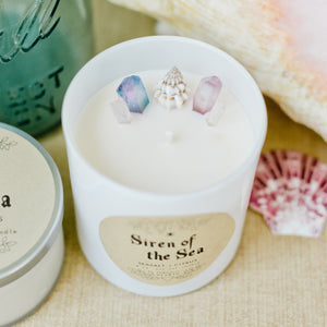 Image of the Siren of the Sea candle by Emerald Hearth.This candle is adorned with titanium-coated, pastel quartz nestled around a seashell to represent the water element.