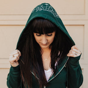 The founder of Emerald Hearth, Brittney wearing the Green Emerald Hearth hoodie and looking down.