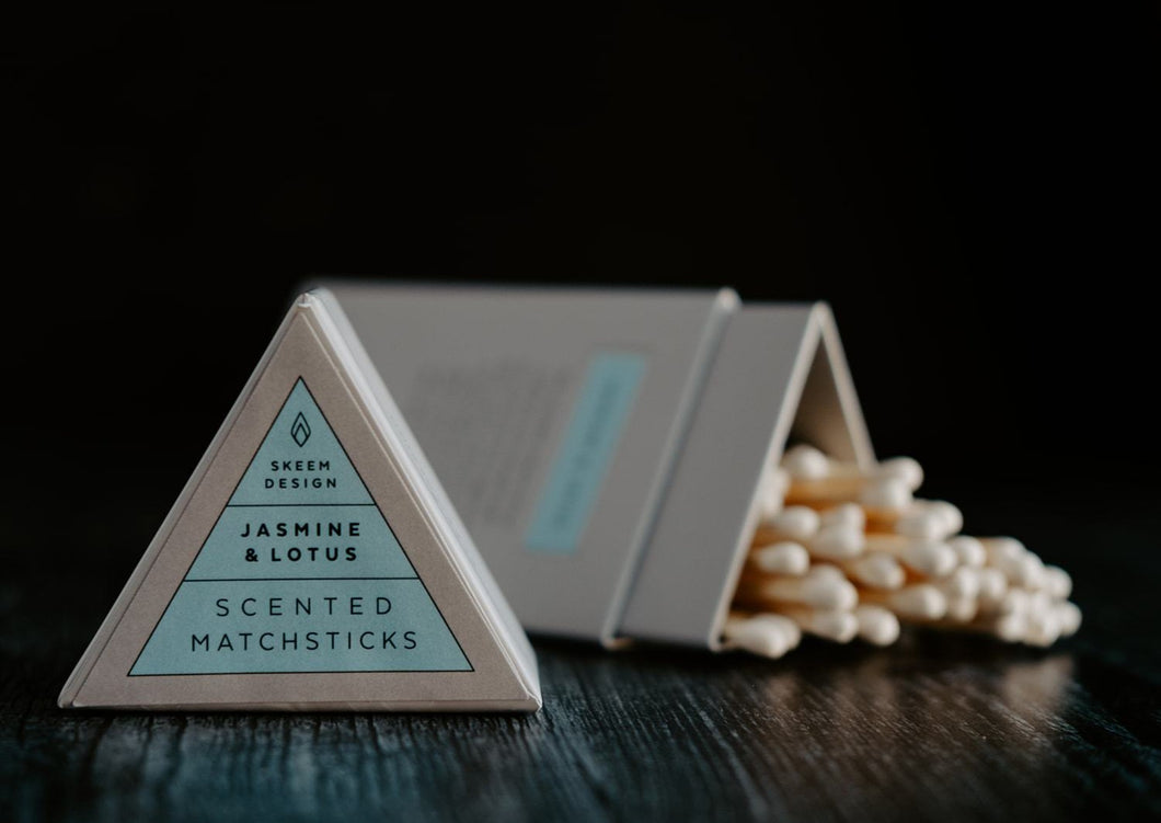 Image of Jasmine & Lotus scented match sticks.  The lid of the triangle packaging is in the foreground and in focus.  The background is of the matches which is out of focus.
