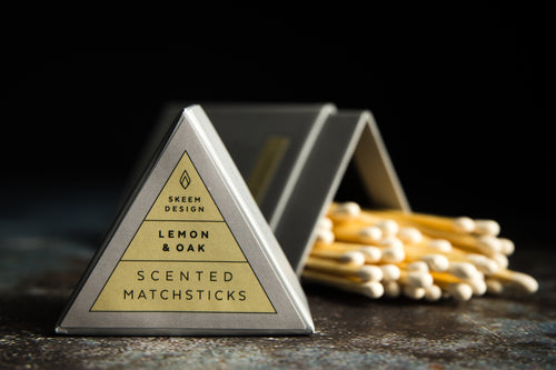 Image of Lemon & Oak scented match sticks.  The lid of the triangle packaging is in the foreground and in focus.  The background is of the matches which is out of focus.