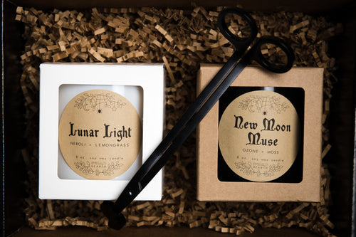 Gift packaged Lunar Love Bundle by Emerald Hearth creations.  The image shows what is included in the bundle.  The Lunar Light candle in white is on the left and the New Moon Muse candle in black is on the right.  On top of the candle is a Emerald Hearth Creations wick trimmer.