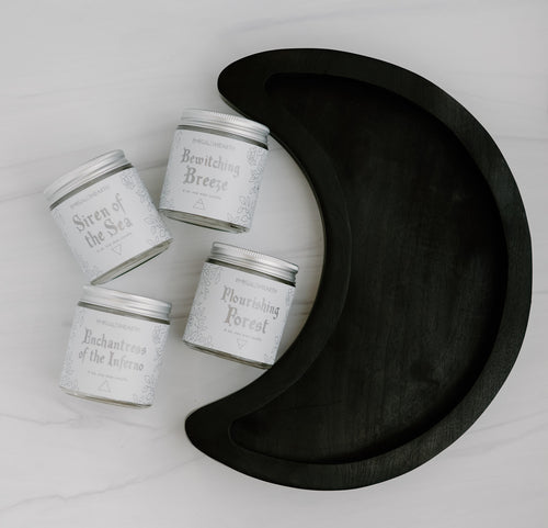 Wooden crescent moon tray displayed with four candles all sold by emerald hearth.  The wooden tray is a crescent moon shape in a dark wood. All five products are on a white background.