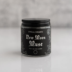 Front view of the New Moon Muse candle by Emerald Hearth.  The candle has black packaging.