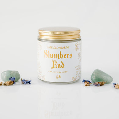 The mini version of the Slumbers End candle by Emerald Hearth Creations.  This ritual equinox candle is photographed against a white background and surrounded by Green Aventurine and violet Forget Me Not flowers.  The candle's packaging is white with gold accents.