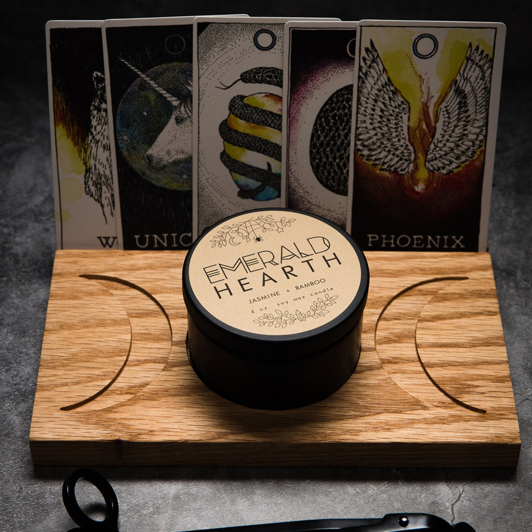 The Large wooden moon stand which has a full moon in the center and a crescent moon facing outward on either side.  The tray has an Emerald Hearth Creations candle in the center.  Behind the tray are five Tarot cards.