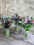 Three Christmas jam jar posies, each creating the essence of the festive season through the use of seasonal British flowers. Imagine these dotted along your Christmas table or by the beds of your guests?