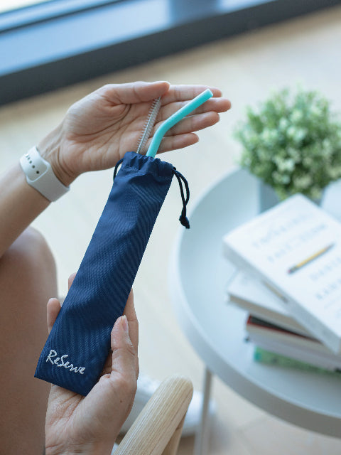 A hand holding the ReServe bag that contains Island Paradise Blue Silicone Reusable Drinking Straw and a cleaning brush.