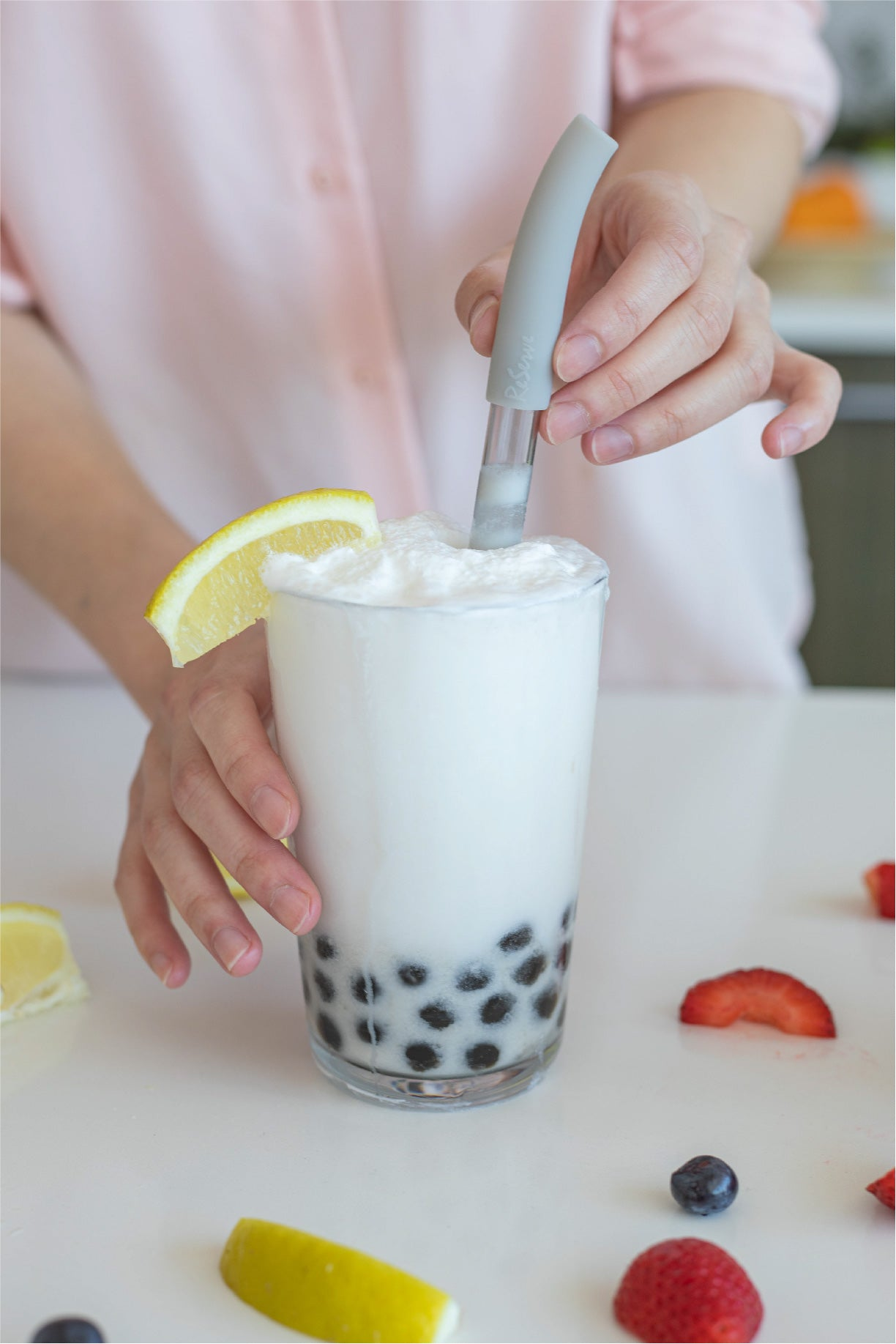 Silver bubble tea straw in a glass of coconut smoothie with pearl