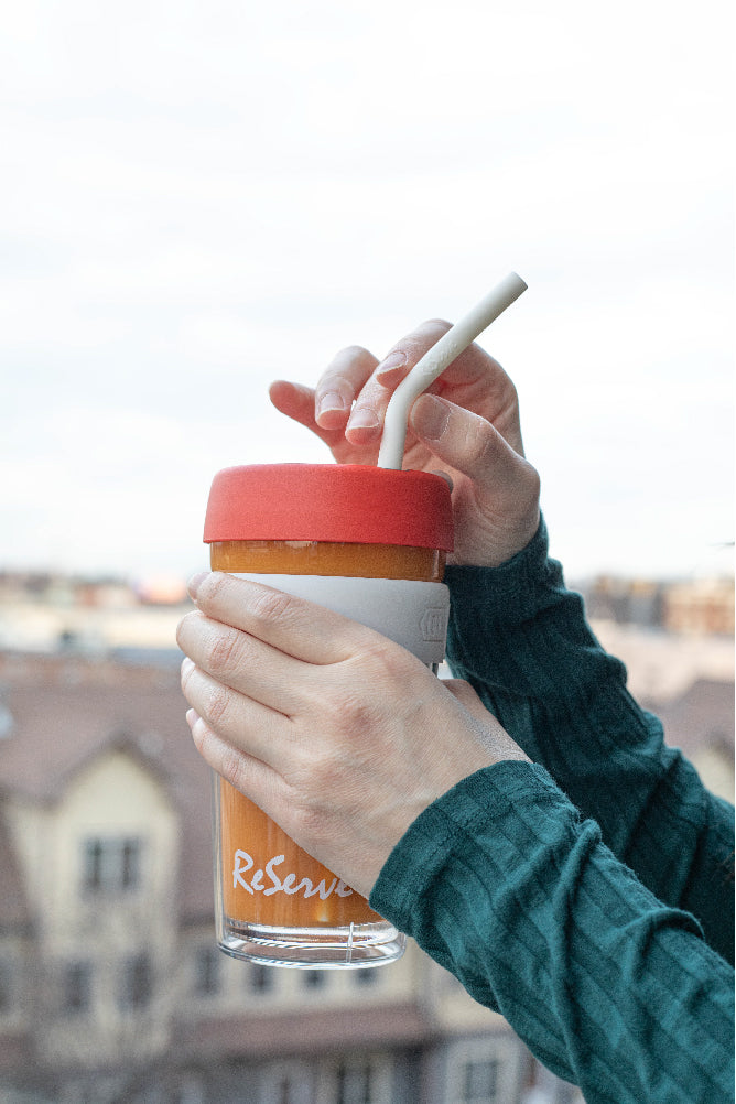 A hand holding Christmas ReServe x KeepCup with Limited-edition ReServe white silicone drinking reusable straw