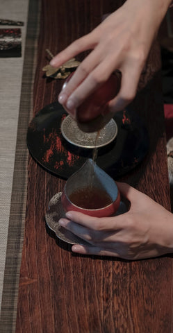 Decant tea from gaiwan to a pitcher, tea ceremony