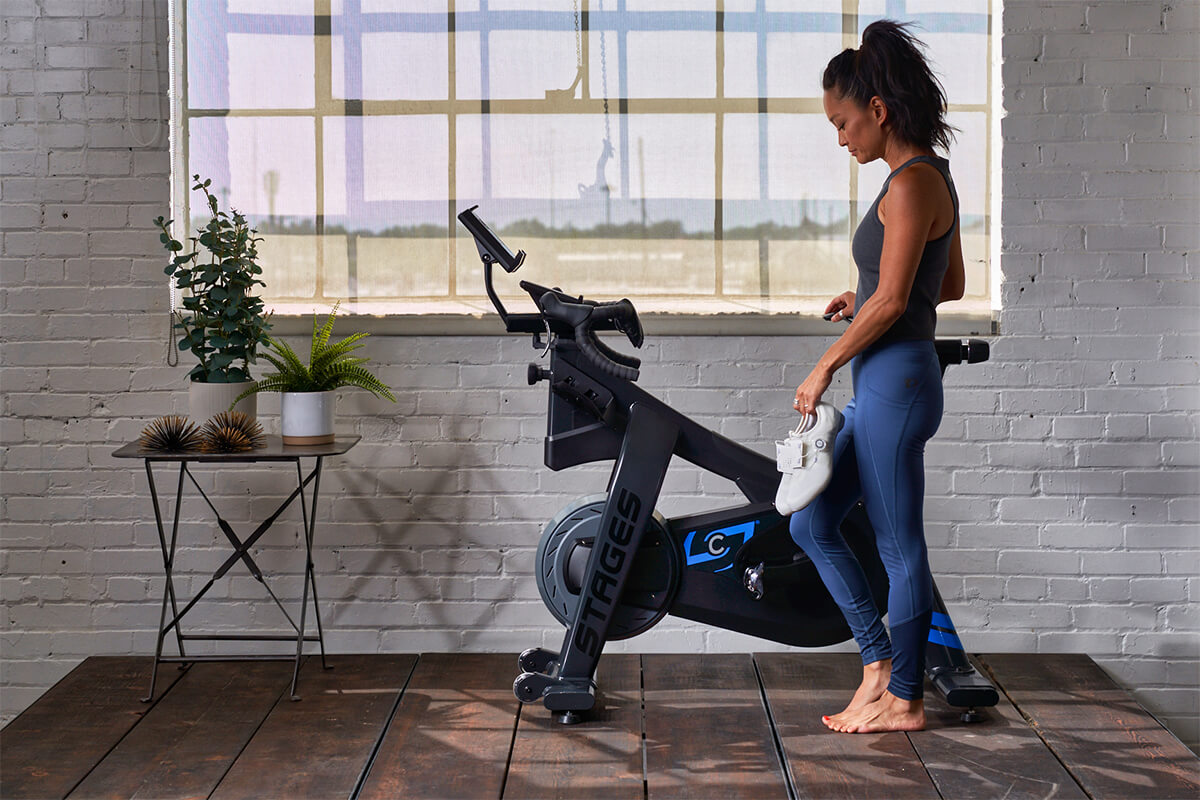 Lady getting ready to ride her indoor cycling bike while holding her Shimao IC500 Indoor Cycling Shoes