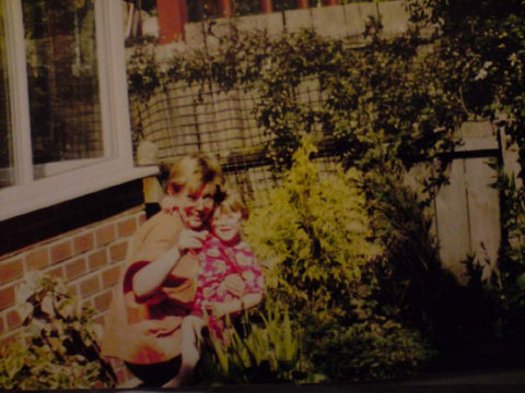 An old photo of Jen Lithgo as a child sat on her Auntie Lou's lap sat around a pond looking at the camera