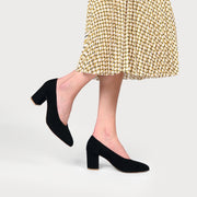black suede heeled court shoes on feet