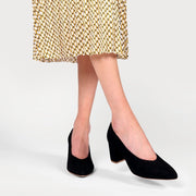 black suede heeled courts on crossed legs
